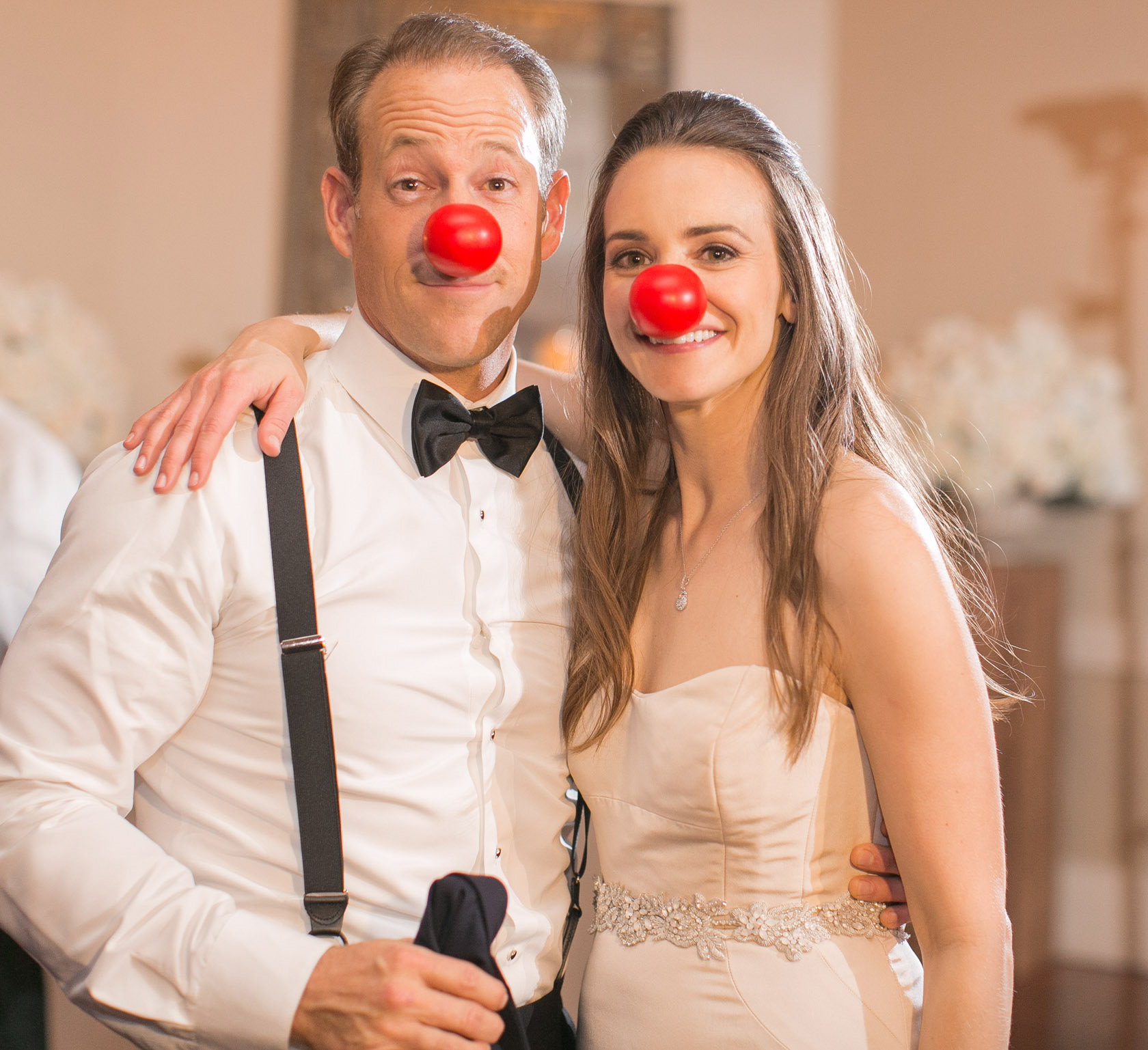 bride and groom clowning around with red clown noses