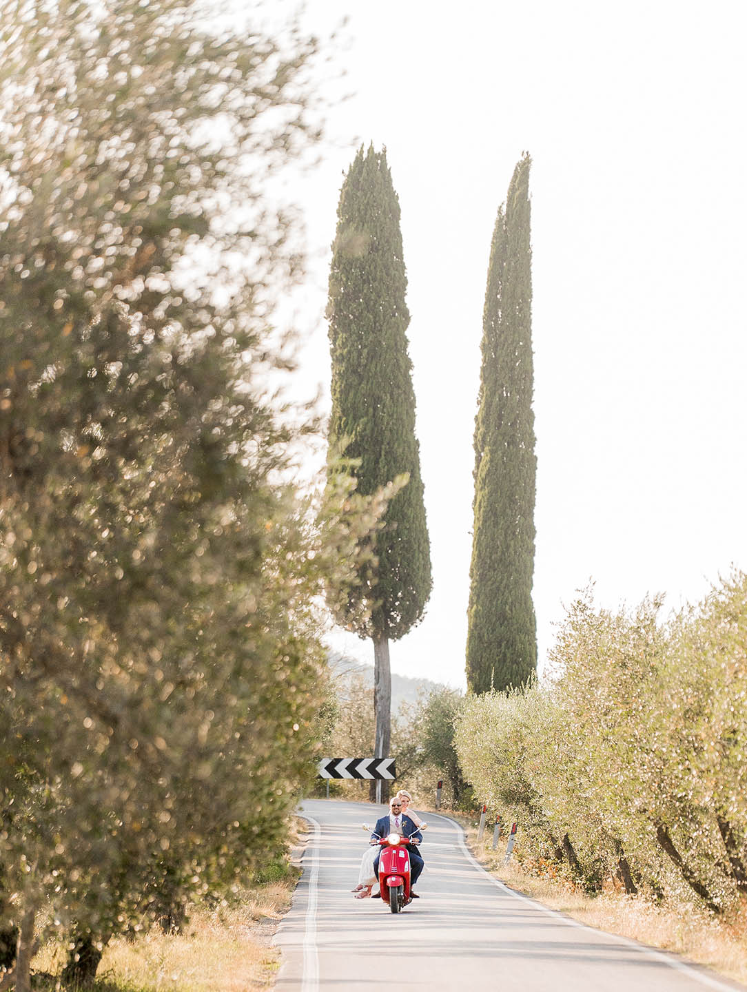 bride and groom riding a vespa in tuscany